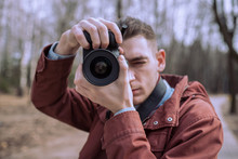 Photographer Pointing Camera At Viewer And Looking Through Lens