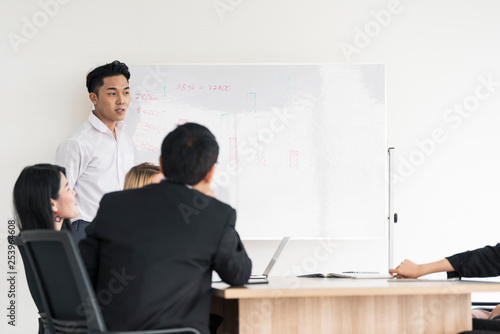 Young asian  businessman present Board project to interested diverse colleagues at office negotiations Canvas Print
