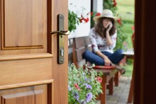 Half Opened Door Into The Beautiful Summer Terrace And  Blooming Garden Where Young Woman Is Sitting, Relaxing And Telephoning.