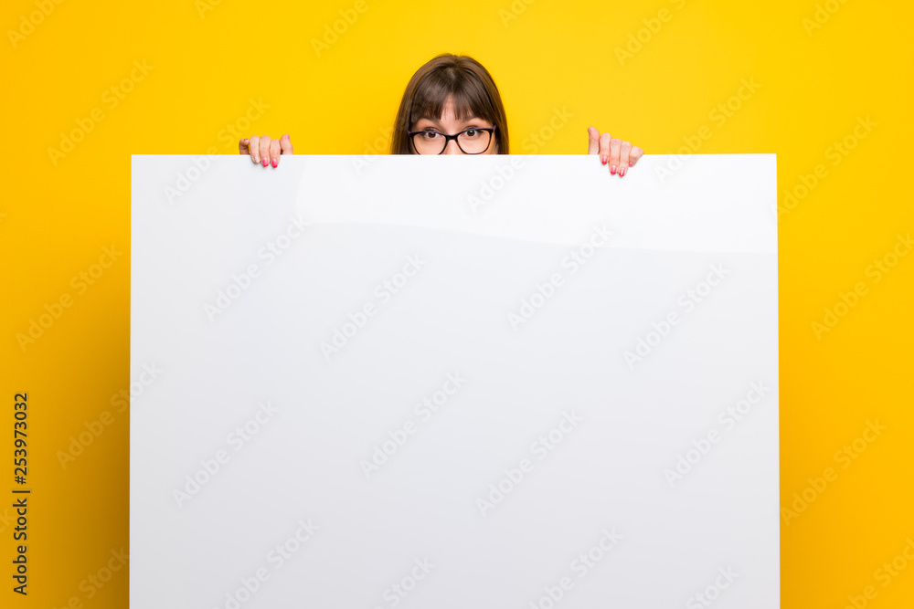 Fototapety, obrazy: Woman with glasses over yellow wall holding a placard for insert a concept