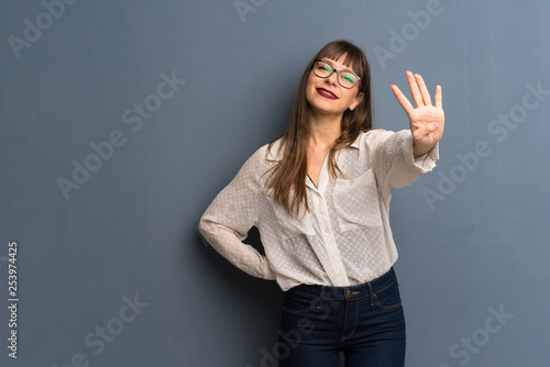 Photographie  Woman with glasses over blue wall happy and counting four with fingers