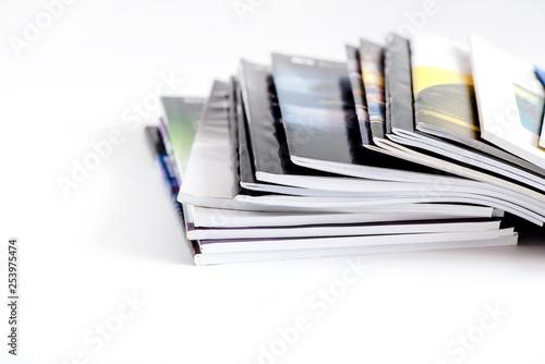 Fotografie, Obraz  Pile of advertising magazines on a white background.