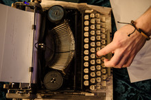 Top View Of Man's Hand Typing On Vintage Typewriter On A Piece Of Newspaper And Dark Blue Velvet Fabric On The Floor