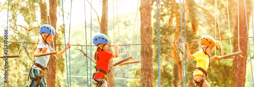 Fotografija  Adventure climbing high wire park - people on course in mountain helmet and safe