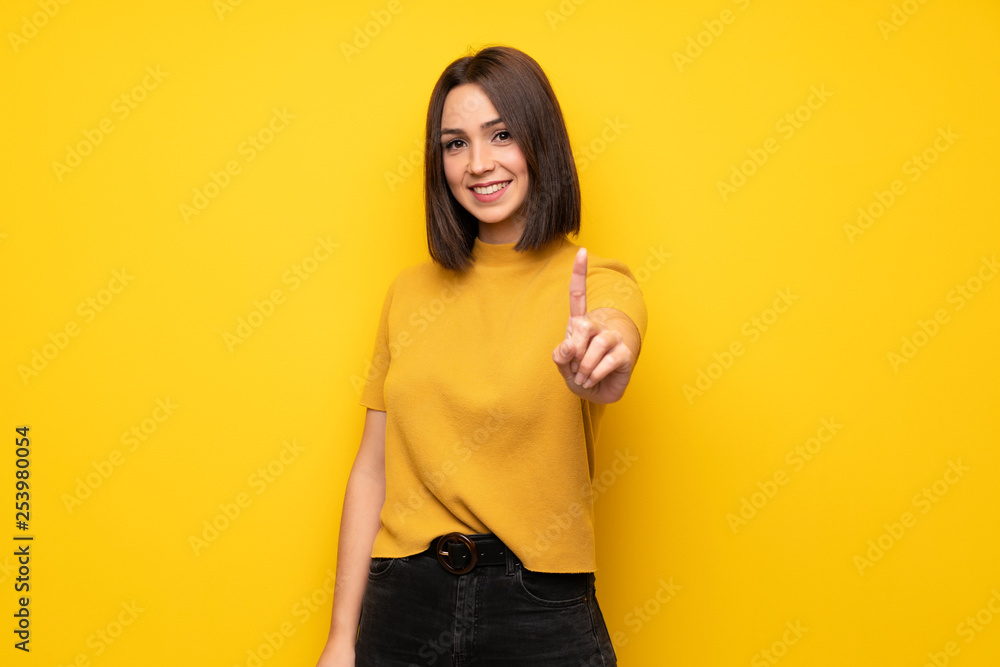 Fototapeta Young woman over yellow wall showing and lifting a finger