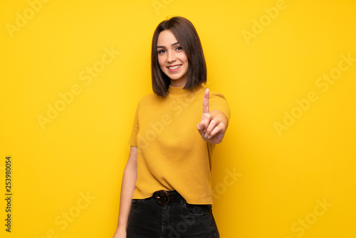 Young woman over yellow wall showing and lifting a finger