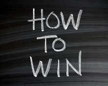 The Words How To Win Written By Hand In White Chalk On A Wiped Blackboard