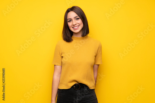 Young woman over yellow wall smiling