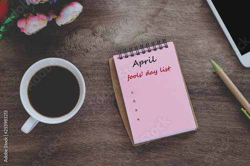 Fotografie, Obraz  April fools' day text list on book note with cup of coffee, pen and smartphone