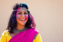 Portrait Of Young Indian Face In Paint Woman In Traditional Indian Pink Outfit With Jeweler Celebrating Holi Color Festival.girl With Black Hair With Bindi On The Head And Snow-white Smile