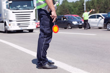Police Officer Controlling Traffic On The Highway