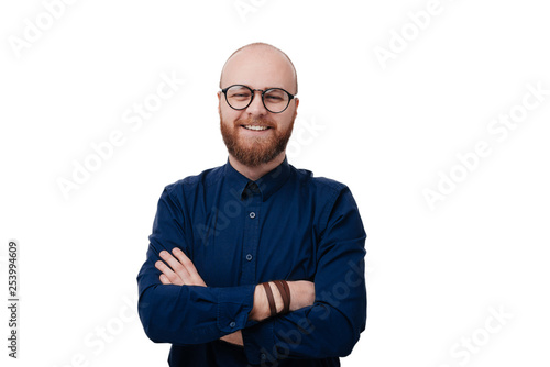 Fotografia  Portrait of happy fashionable bearded man with eyeglassees crossing hands and lo