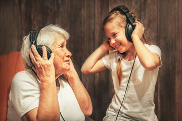 old woman and little girl in headphones listening to music grandmother and granddaughter
