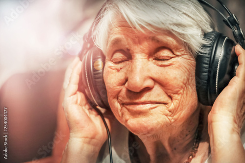 old woman in headphones listening to music - 254004477