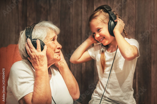 old woman and little girl in headphones listening to music grandmother and grand Canvas Print