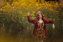 The Girl Is A Scarecrow In A Field With Yellow Flowers.