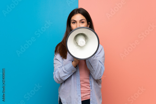 Young woman over pink and blue wall shouting through a megaphone Wallpaper Mural