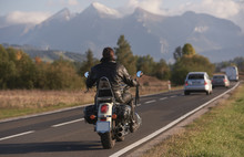 Back View Of Biker In Black Leather Jacket Riding Motorcycle Along Road On Blurred Background Of Beautiful Mountain Range With Snowy Peaks, Moving Vehicles On Bright Sunny Summer Evening.