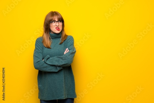 Pinturas sobre lienzo  Woman with glasses over yellow wall with confuse face expression while bites lip
