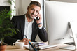 Image of happy businessman talking on cell phone while working on computer in office