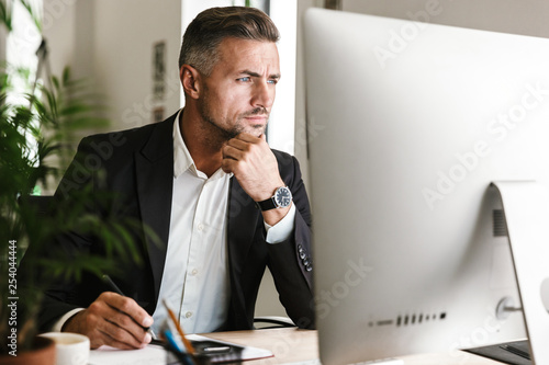 Image of confident businessman working in office and looking on computer Fototapet