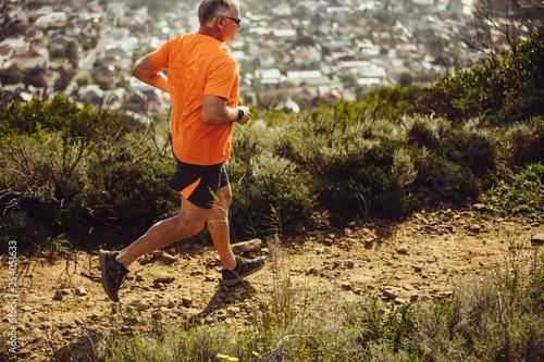 Sportowy mężczyzna biegający na wzgórzu