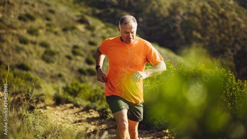 Poster Jogging Senior athletic person trail running on a hill