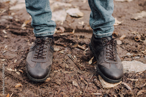 Canvas Prints Countryside A man in a blue suit ties up shoelaces on brown leather shoes brogues on a wooden parquet