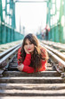 Beautiful Young Woman Lying Down on the Train Tracks.