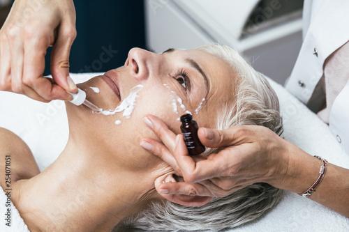 Fotografia  Beautiful senior woman face during facial treatment at luxury beauty clinic