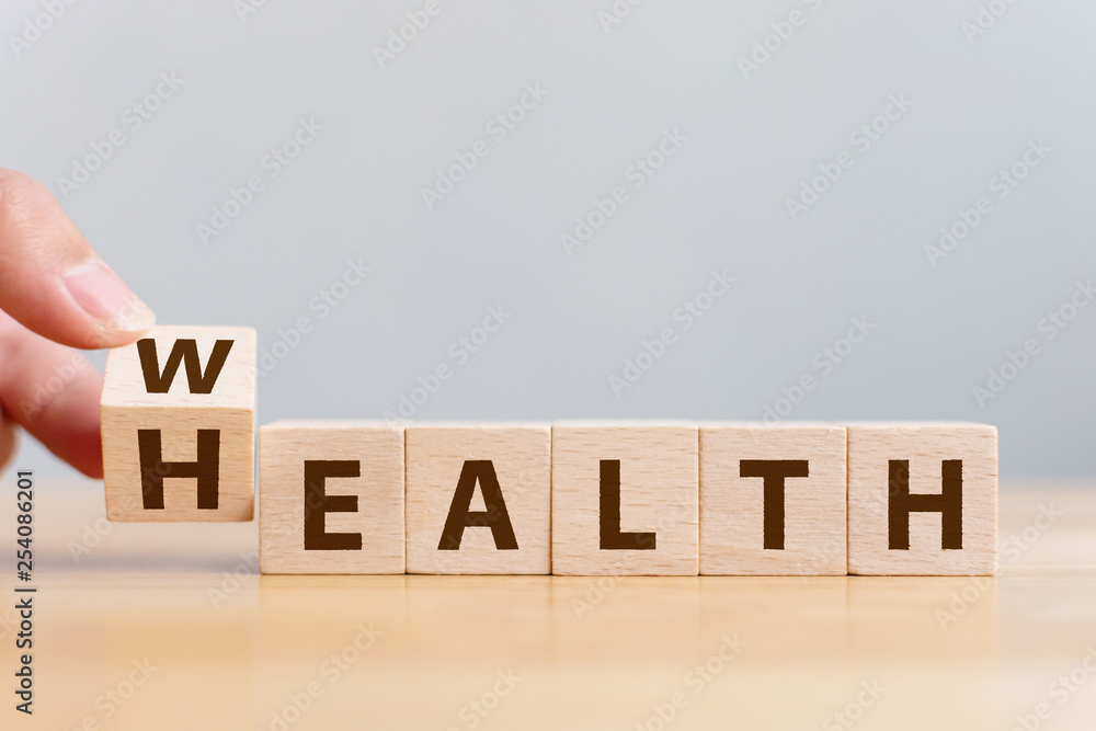 Fototapeta Hand flip wooden cube with word wealth to health. Investment in life insurance and healthcare concept