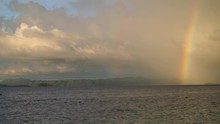 A Rainbow In The Background As A Traditional Small Wooden Boat Is Driving Pass Out Of Frame.