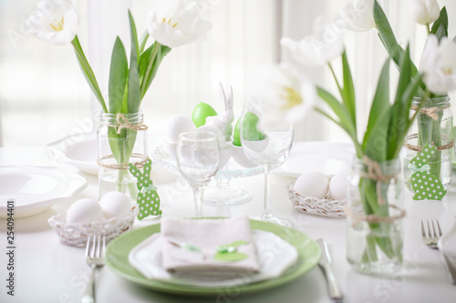 Fototapety, obrazy: Decor and table setting of the Easter table with white tulips and dishes of green and white color. Easter decor in the form of Easter bunnies  green color with white polka dots.