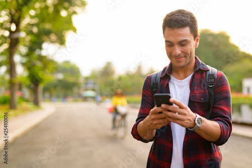 Fotografie, Obraz  Happy young handsome Hispanic hipster man using phone at the park