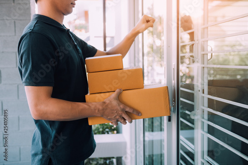 Young asian courier is using the hand of the knock at the door to deliver the goods Fototapet