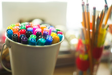 Bucket Of Markers And Pencils On Desk