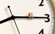 canvas print picture - A miniature old couple sitting on a clock's needle.