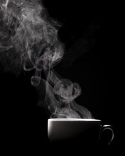 Steaming Coffee In Cup Isolated On Black Background With Copy Space.