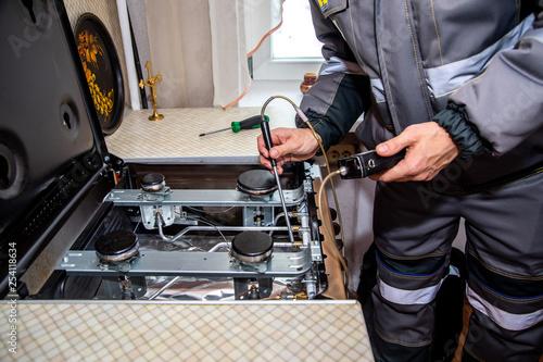 Fotografija MINSK, BELARUS - 18 FEBRUARY, 2019: gas worker checks the gas stove