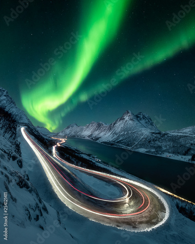 Photo sur Toile Aurore polaire Northern lights over mountain pass road composite, light trails on highway under dramatic aurora borealis sky