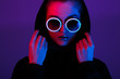 canvas print picture - Portrait of fashion young girl in a black sweater with a hood and round sunglasses in red and blue neon light in the studio