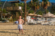 tanned seven-year-old boy in white beach shorts holding a volleyball ball on the sand