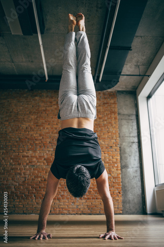 Canvas Print Young man doing yoga handstand in big bright training gym