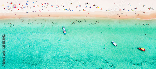 In de dag Strand View from above, stunning aerial view of a beautiful tropical beach with white sand and turquoise clear water, long-tail boat and people sunbathing, Surin beach, Phuket, Thailand.