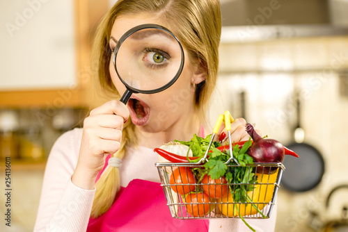 Fotografía  Woman investigating shopping backet with vegetables
