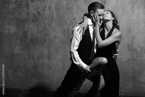 Photo  Young pretty female tango dancer in black dress and male dancing tango