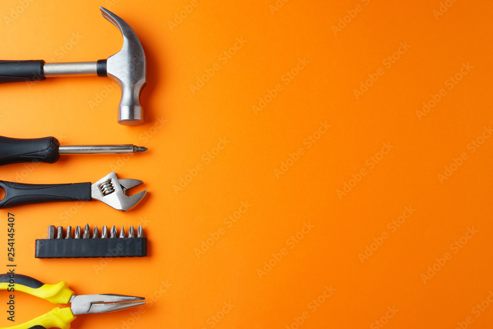 Fotografía  Hammer, pliers, screwdriver on an orange background, top view, a place for an in