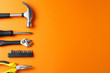 canvas print picture - Hammer, pliers, screwdriver on an orange background, top view, a place for an inscription