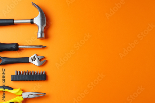 Pinturas sobre lienzo  Hammer, pliers, screwdriver on an orange background, top view, a place for an in