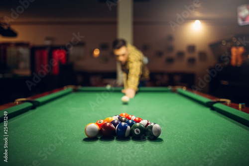 Male billiard player with cue aiming at the table Fototapete